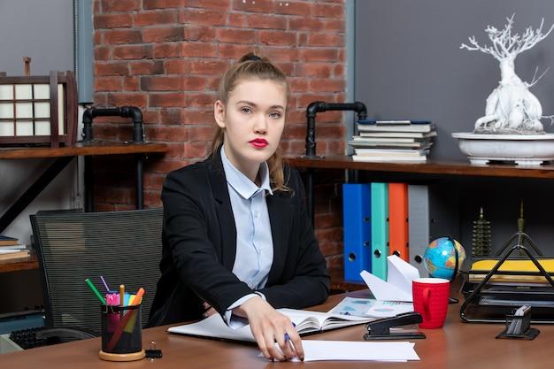 Draufsicht einer jungen selbstbewussten assistentin, die an ihrem schreibtisch im büro sitzt