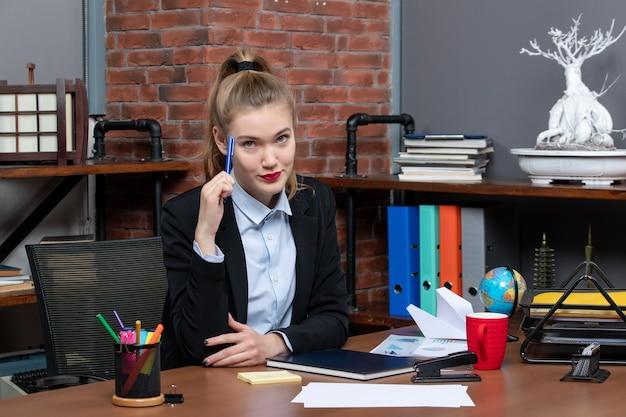 Draufsicht einer jungen selbstbewussten und entschlossenen assistentin, die an ihrem schreibtisch im büro sitzt sitting
