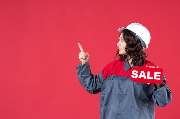 Draufsicht einer konzentrierten baumeisterin in uniform, die einen schutzhelm trägt und das verkaufssymbol auf der rechten seite auf isoliertem rotem hintergrund zeigt