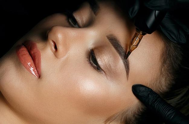 Draufsicht einer kosmetikerin, die permanentes make-up der augenbrauen auf dem gesicht der frau macht