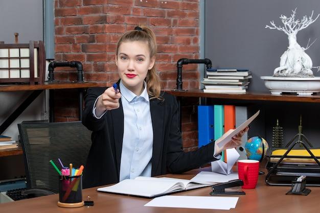 Draufsicht einer lächelnden jungen frau, die an einem tisch sitzt und ein dokument hält, das im büro auf einen blauen farbstift zeigt