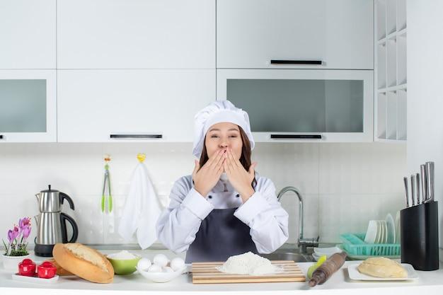 Draufsicht einer lächelnden köchin in uniform, die hinter dem tisch mit schneidebrettbrotgemüse steht und kussgeste macht
