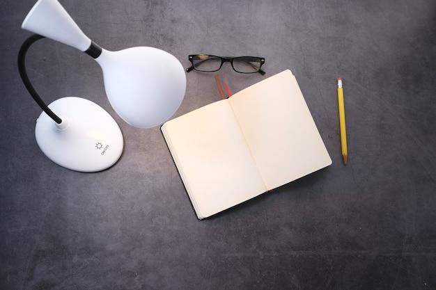 Draufsicht einer lampe, eines tagebuchs und eines bleistifts auf fliesenhintergrund