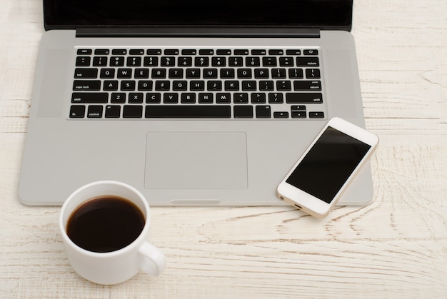 Draufsicht einer laptoptastatur, des intelligenten telefons und des tasse kaffees
