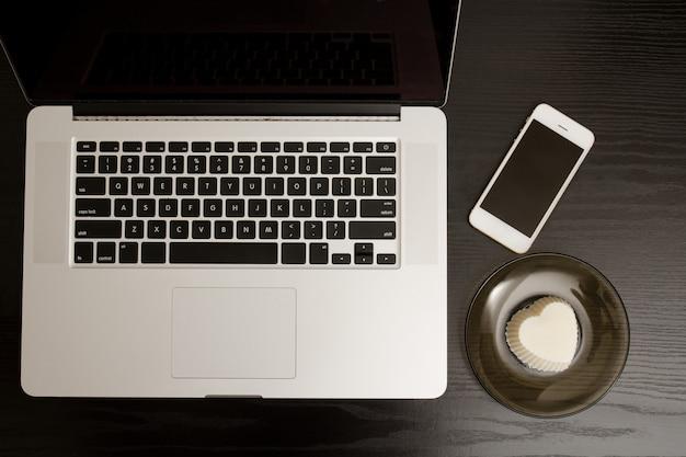 Draufsicht einer laptoptastatur, des smartphone und des nachtischs auf einem schwarzen holztisch