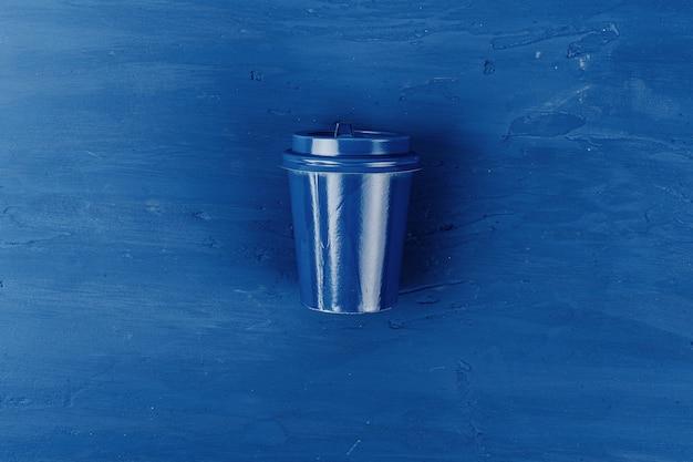 Draufsicht einer mitnehmerkaffeetasse auf klassischem blauem hintergrund