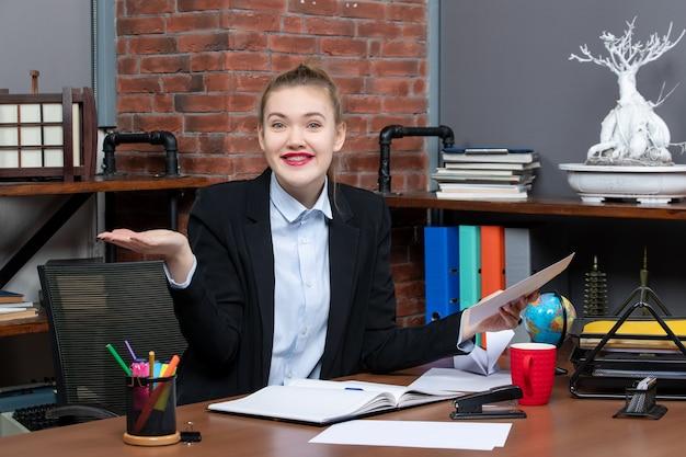 Draufsicht einer neugierigen jungen frau, die an einem tisch sitzt und ein dokument im büro hält