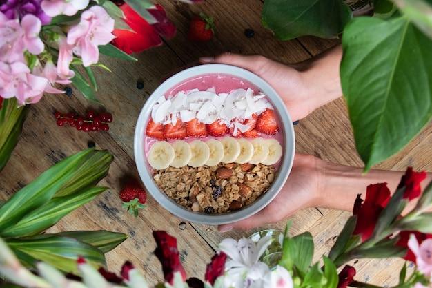 Draufsicht einer person, die eine gesunde smoothie-schüssel mit früchten und müsli hält