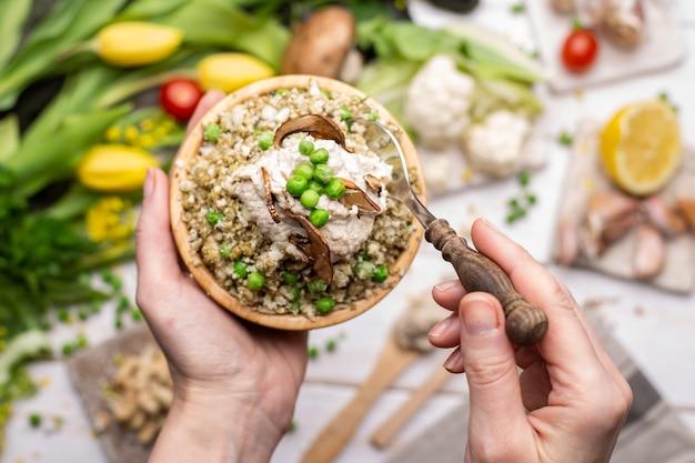 Draufsicht einer person, die eine schüssel mit köstlichem veganem salat hält holding