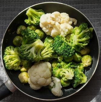 Draufsicht einer pfanne mit frischem aufgetautem gemüse: blumenkohl, brokkoli