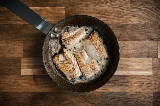 Draufsicht einer pfanne mit gebratenem fleisch auf einem holztisch
