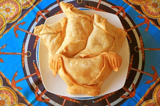 Draufsicht einer platte von chilenischen empanadas oder von wohlschmeckendem angefülltem gebäck