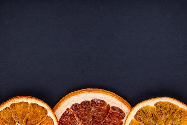 Draufsicht einer reihe von getrockneten scheiben von orange und grapefruit angeordnet auf schwarzem hintergrund