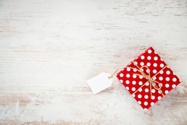 Draufsicht einer rot punktierten geschenkbox über weißem holz, copyspace. leere notiz.