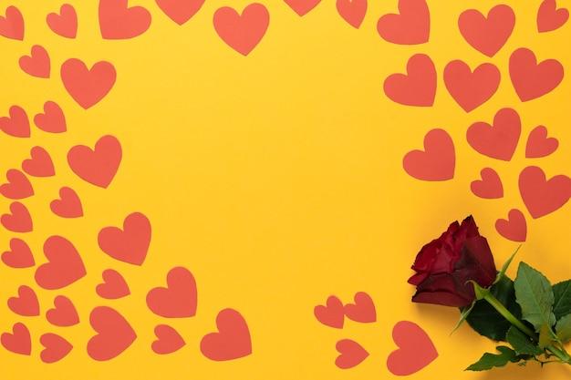 Draufsicht einer roten rose liegt auf gelbem grund. viele rote pappherzen in verschiedenen größen