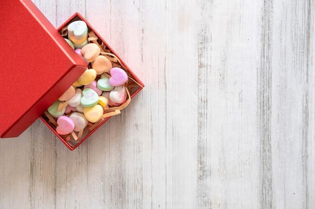 Draufsicht einer roten schachtel mit kleinen bonbons in form eines herzens in pastellfarben