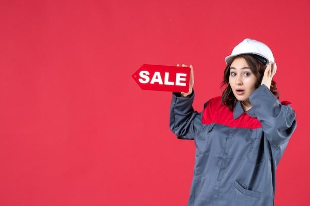 Draufsicht einer schockierten arbeiterin in uniform, die einen schutzhelm trägt und das verkaufssymbol auf isoliertem rotem hintergrund zeigt