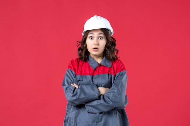 Draufsicht einer schockierten baumeisterin in uniform mit schutzhelm auf isoliertem rotem hintergrund