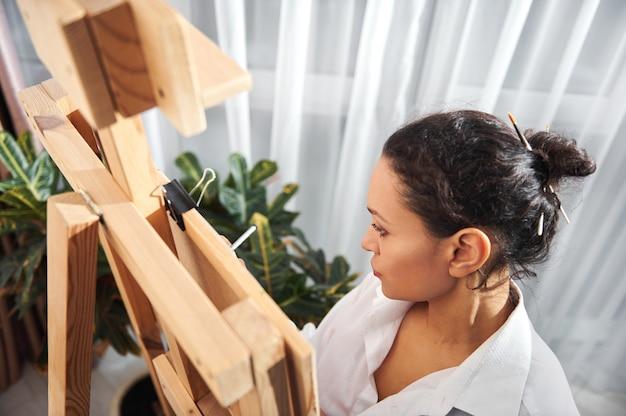 Draufsicht einer schönen brünetten malerin mit gesammelten haaren in einem brötchen und pinseln in ihren haaren, die vor der staffelei in werkstatt und zeichnung stehen