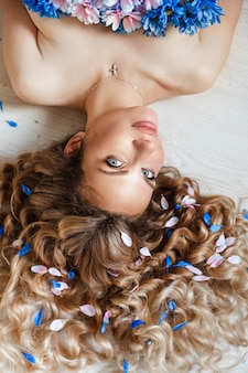 Draufsicht einer schönen dame, die ruhig mit blütenblättern der blumen in ihrem langen herrlichen haar liegt. schönheitskonzept