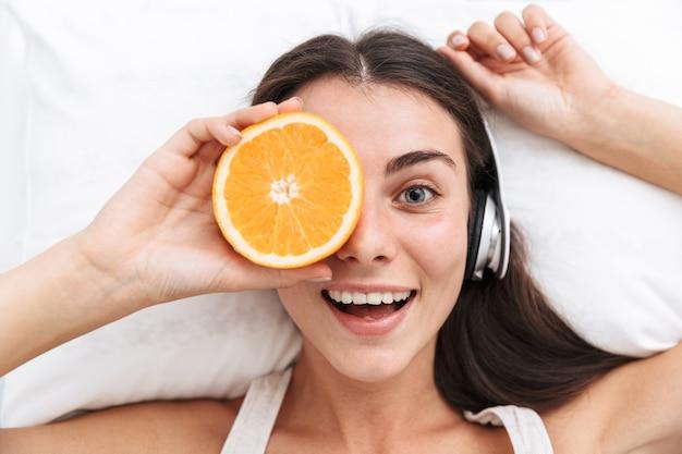 Draufsicht einer schönen jungen frau, die musik mit kopfhörern hört, während im bett liegend, geschnittene orange hält