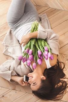 Draufsicht einer schönheit, die am handy spricht und blumen hält. fröhliches junges mädchen mit tulpen