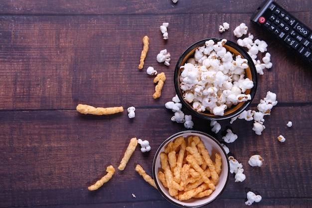 Draufsicht einer schüssel popcorn, chips und fernsehfernbedienung auf hölzernem hintergrund