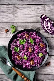 Draufsicht einer schwarzen platte mit köstlichem rotkohlsalat auf rustikalem grauem hölzernem hintergrund