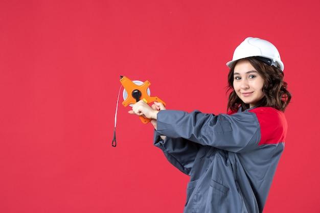 Draufsicht einer selbstbewussten architektin in uniform mit schutzhelm, die maßband auf isoliertem rotem hintergrund hält