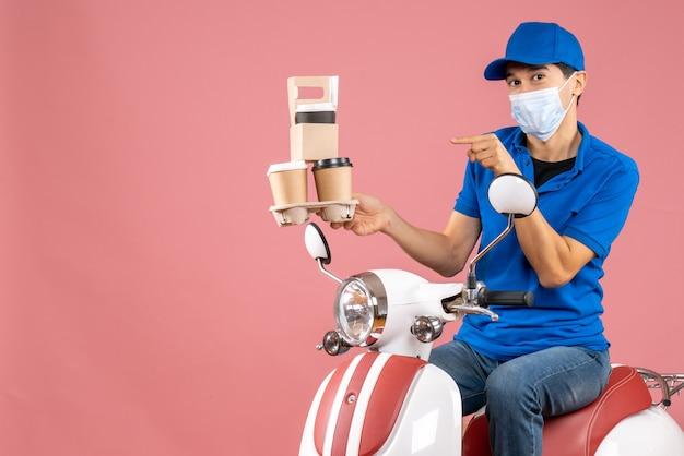 Draufsicht einer selbstbewussten männlichen lieferperson in maske mit hut, die auf einem roller sitzt und bestellungen auf pfirsichhintergrund liefert