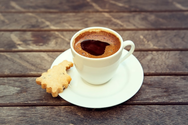 Draufsicht einer tasse kaffee auf einem hölzernen hintergrund. kleiner starker schwarzer espresso auf holztisch.