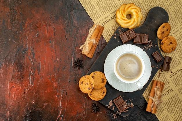 Draufsicht einer tasse kaffee auf einem holzbrett auf einem alten zeitungskekse zimt-limonen-schokoriegel auf der linken seite auf dunklem hintergrund