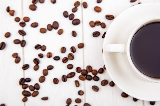 Draufsicht einer tasse kaffee mit kaffeebohnen lokalisiert auf einem weißen hölzernen hintergrund