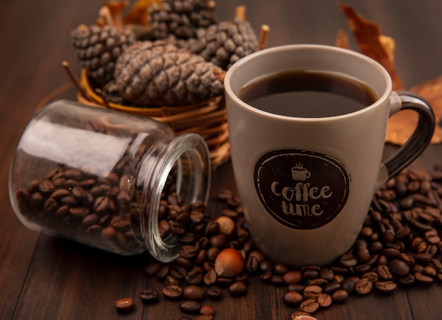 Draufsicht einer tasse kaffee mit tannenzapfen auf einem eimer mit kaffeebohnen, die aus glas auf einer holzoberfläche fallen