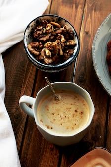 Draufsicht einer tasse kaffee mit walnüssen in einer schüssel