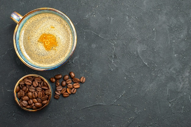 Draufsicht einer tasse kaffeeschale mit kaffeesamen auf dunklem, isoliertem hintergrund