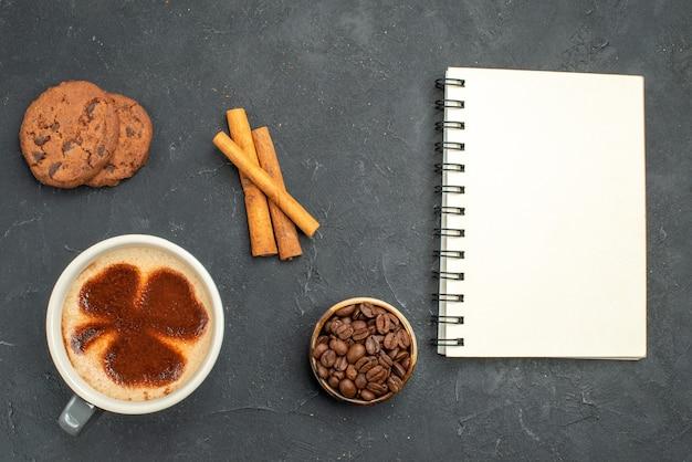 Draufsicht einer tasse kaffeeschale mit kaffeesamen zimtstangen ein notizbuch auf dunklem, isoliertem hintergrund