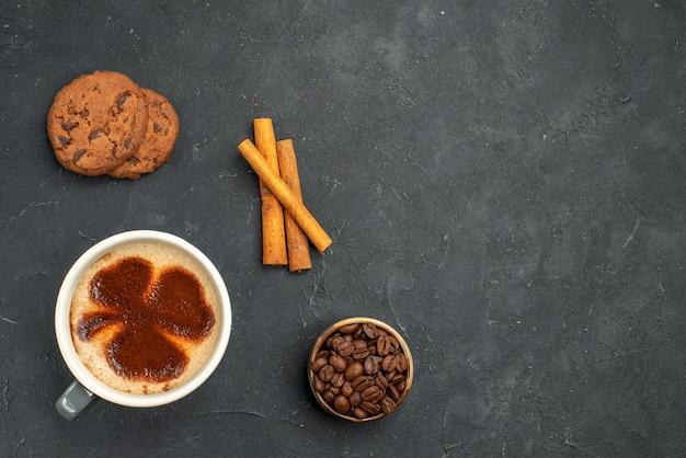 Draufsicht einer tasse kaffeeschale mit kaffeesamen zimtstangen kekse auf dunklem, isoliertem hintergrund