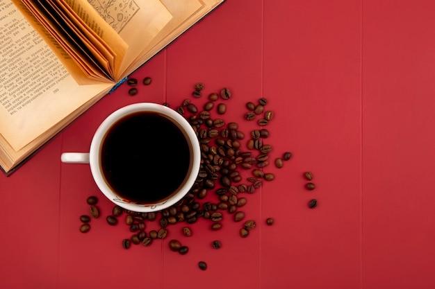 Draufsicht einer tasse köstlichen kaffees mit kaffeebohnen lokalisiert auf einem res hintergrund mit kopienraum