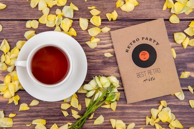 Draufsicht einer tasse schwarzen und leckeren tees mit gelben blütenblättern lokalisiert auf holz