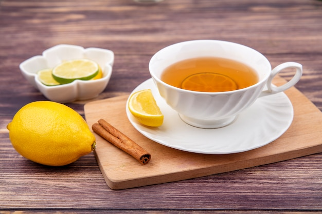 Draufsicht einer tasse tee auf hölzernem küchenbrett mit zitronen-zimtstange auf holz