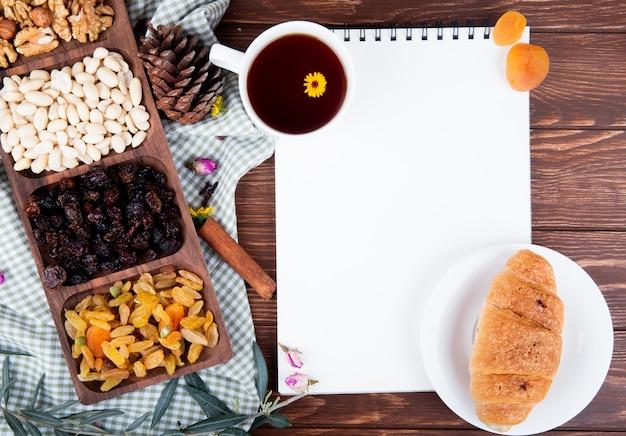 Draufsicht einer tasse tee mit einem skizzenbuch, croissant auf einem teller, gemischte nüsse mit getrockneten früchten auf holz