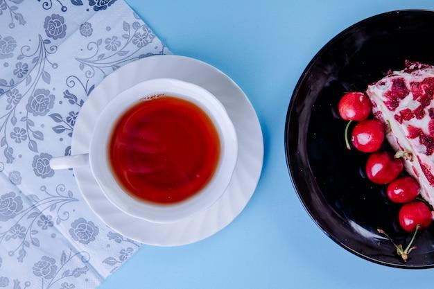 Draufsicht einer tasse tee mit einem stück kuchen, das mit frischen roten kirschen auf schwarzem teller auf blau verziert wird