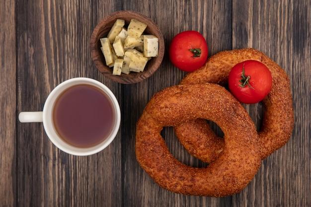 Draufsicht einer tasse tee mit frischem türkischem bagel und gehackten käsescheiben auf einem hölzernen hintergrund