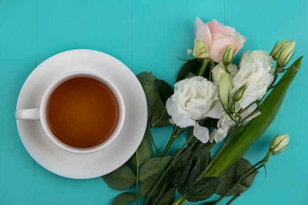 Draufsicht einer tasse tee mit frischen schönen blumen und blättern auf einem blauen hintergrund