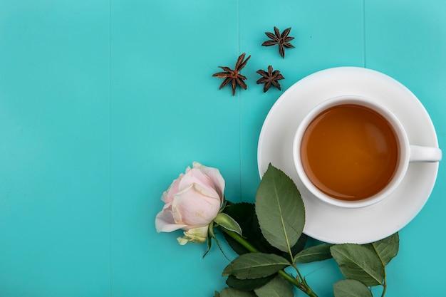Draufsicht einer tasse tee mit frischer rosa rose auf einem blauen hintergrund mit kopienraum