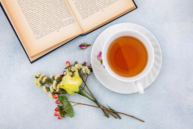 Draufsicht einer tasse tee mit gelber rose mit hypericum-beeren auf weiß