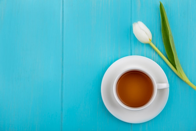 Draufsicht einer tasse tee mit schöner weißer tulpe auf einem blauen hölzernen hintergrund mit kopienraum