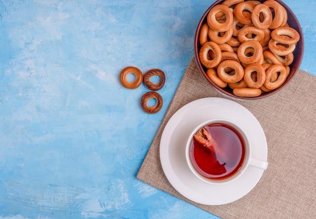 Draufsicht einer tasse tee mit zimtstange und einer schüssel mit brotringen auf blauem hintergrund