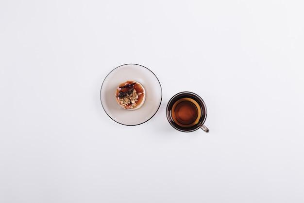 Draufsicht einer tasse tee und des kuchens auf der untertasse auf tabelle